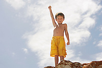 Smiling boy (5-6) standing on rock on beach low angle view