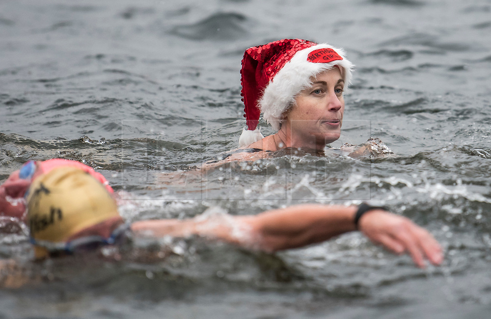 © Licensed to London News Pictures. 25/12/2017. London, UK. A competitor wearing Santa hat as members of the Serpentine Swimming Club brave the cold waters at the Serpentine Lake in Hyde Park, London to compete for the traditional Peter Pan Cup on Christmas Day, December 25, 2017. Photo credit: Ben Cawthra/LNP