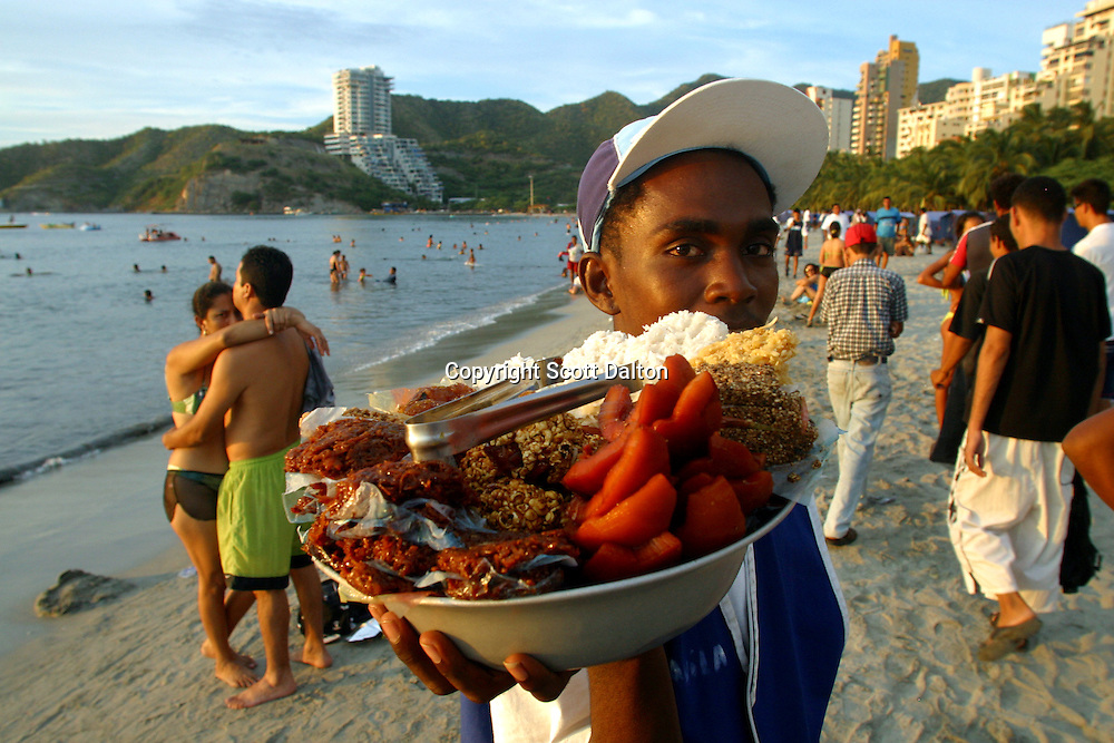 A vender tries to sell treats on the beach in El Rodadero, just outside of Santa Marta on Colombia's Caribbean coast, on Monday, December 12, 2005. The government has increased security along the countries highways and now more and more Colombians are starting to travel to popular destinations throughout the country. (Photo/Scott Dalton)