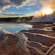 Yellowstone National Park's Midway Geyser Basin is a hotbed of thermal activity. Two very different hot springs share the morning's light: Turquoise Pool, reflecting clouds and sky, and Excelsior Geyser, which boils and steams most of the time.