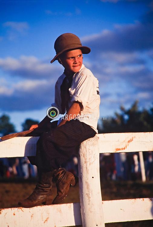 Rio Grande do Sul, Brasil. 1999..Crianca com roupa tipica de gaucho assiste rodeio do alto da cerca./ Child with typical clothes of gaucho attends rodeo of the high one of the fence..Foto ©Adri Felden/Argosfoto