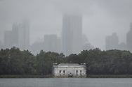 Mid-Manhattan skyscrapers looming up in the mist at The South Gatehouse at the Reservoir in Central Park.