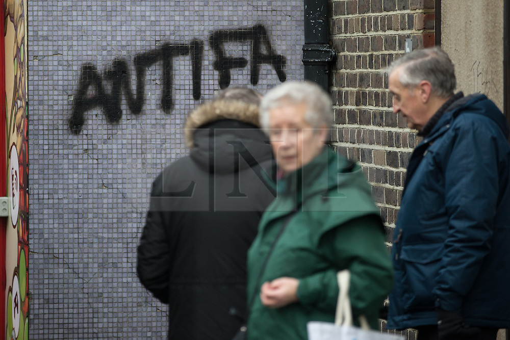 "© Licensed to London News Pictures . 30/01/2016 . Dover , UK . People queue at a bus stop next to anti-fascist graffiti reading "" ANTIFA "" ahead of demonstrations by far-right groups (including The National Front , The North West Infidels and The South East Alliance ) and , opposing them , anti-fascists , close to the port of Dover in Kent . Photo credit : Joel Goodman/LNP"