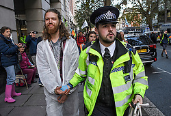 © Licensed to London News Pictures. 08/10/2019. London, UK. An Extinction Rebellion activist being arrested after glueing himself to the Department for Transport in Westminster. Activists have converged on Westminster for a second day, blockading roads in the area and calling on government departments to 'Tell the Truth' about what they are doing to tackle the Emergency. Photo credit: Ben Cawthra/LNP