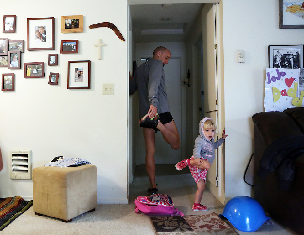 At age 31 Alan Webb, an elite distance runner and the holder of the American record in the mile, is attempting to transform into a triathlete. He trains by swimming, bicycling and running with his family in Beaverton, Ore. Here he stretches before a run with his two-year-old daughter Joanie.