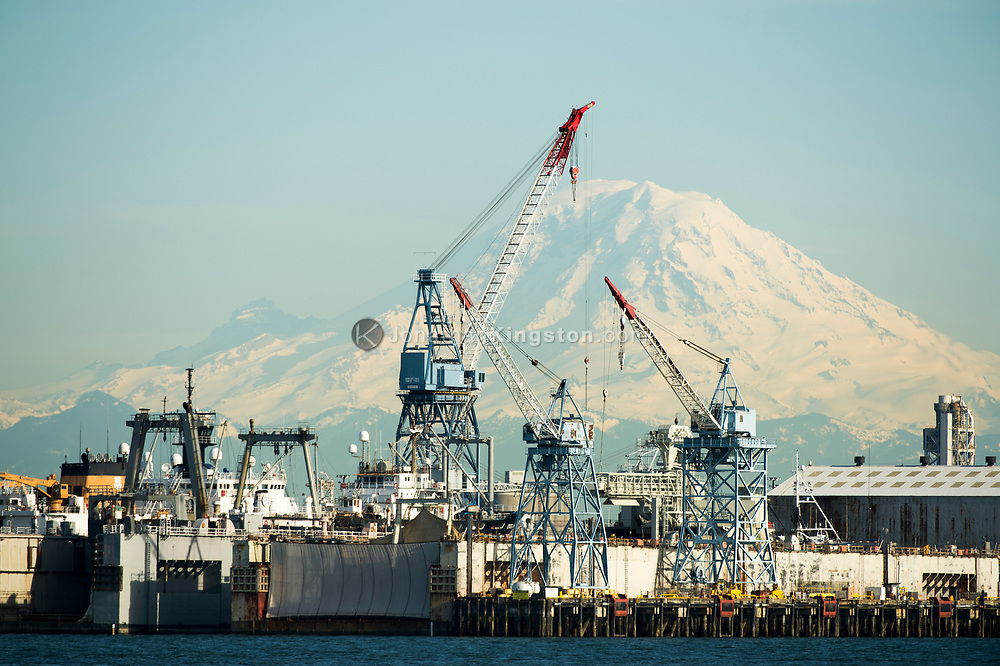 Harbor cranes in the port of Seattle in front of Mt Rainier.
