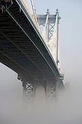 Manhattan bridge in early morning fog seen from Brooklyn site