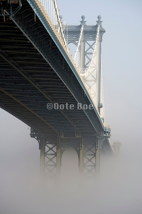 Manhattan bridge in early morning fog seen from Brooklyn site