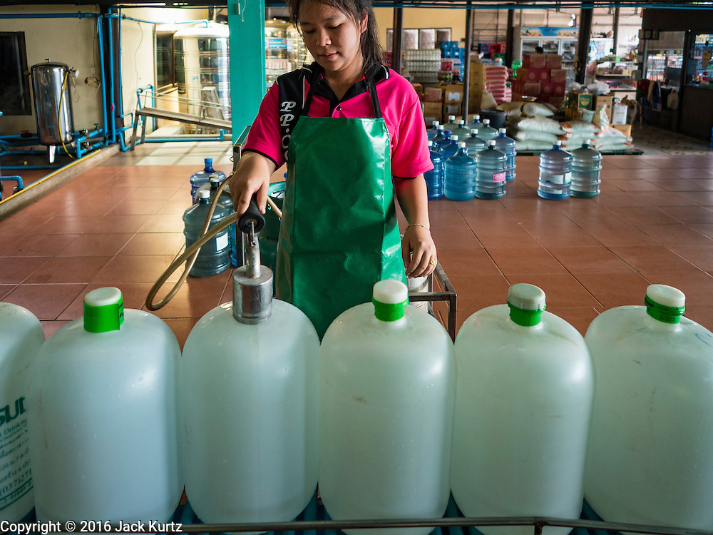 16 MARCH 2016 - BAN SONG, PRACHIN BURI, THAILAND: A worker seals bottles of water at a water bottling plant in Ban Song. The plant has been open for 11 years and is reporting that demand has increased above normal this year because more people are buying bottled water because salt water has intruded into the local water supply. Some people are buying the bottled water to wash and bathe with because of the salt water intrusion. The drought in Thailand is worsening and has spread to 14 provinces in the agricultural heartland of Thailand. Communities along the Bang Pakong River, which flows into the Gulf of Siam, have been especially hard hit since salt water has intruded into domestic water supplies as far upstream as Prachin Buri, about 100 miles from the mouth of the river at the Gulf of Siam. Water is being trucked to hospitals in the area because they can't use the salty water.    PHOTO BY JACK KURTZ