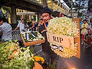 18 AUGUST 2015 - BANGKOK, THAILAND:  A man brings flowers, including a wreath that says RIP, to a makeshift memorial in front of Erawan Shrine, which was damaged by a bomb Monday night. An explosion at Erawan Shrine, a popular tourist attraction and important religious shrine in the heart of the Bangkok shopping district, killed at least 20 people and injured more than 120 others, including foreign tourists, during the Monday evening rush hour. Twelve of the dead were killed at the scene. Thai police said an Improvised Explosive Device (IED) was detonated at 18.55. Police said the bomb was made of more than six pounds of explosives stuffed in a pipe and wrapped with white cloth. Its destructive radius was estimated at 100 meters.    PHOTO BY JACK KURTZ