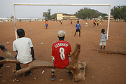 Spectator in Liverpoll FC Steven Gerrad shirt watching Football practice and training for the under 12's team of Corners Babies youth football Academy. Two of the academy's past players now play for the national team, the Black Stars.  Kumasi- Ghana's second largest city. West Africa..©Picture Zute Lightfoot.  07939 108077. www.lightfootphoto.co.uk