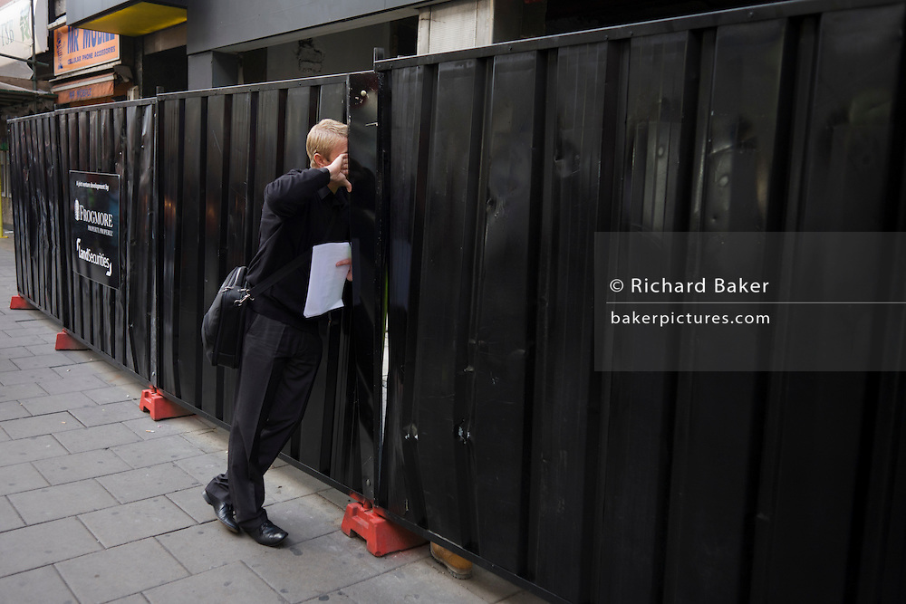 A man in a central London street speaks through a gap in construction sheeting to a hidden colleage whose boots are seen below.