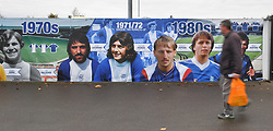 A fan walks past a timeline mural outside St Andrews, home of Birmingham City