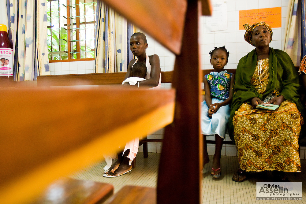 Ahoua Konante (right) waits with her seven-year-old daughter Aishata, who suffers from fever, cough and muscle pains, at the NDA health center in Dimbokro, Cote d'Ivoire on Friday June 19, 2009.
