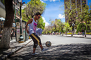 Jorge Villa plays football on 16th July Avenue in central La Paz. During a normal day it would be impossible since this avenue is one of the main arteries of La Paz. During elections period in  Bolivia, the country faces several restrictions, like no alcohol for sale 48 hours before and 12 after the election; no public gatherings, shows of any kind until the political parties made their speeches on the election night; its completely forbidden the circulation of any vehicles, private or governmental except with the permit from the Electoral Tribunal, which means it would be basically no cars, buses or anything circulating in the city; no long distance buses, the terminal will be close from Saturday until Monday and even flights will not be allowed except the ones leaving the country or the international ones doing stop-over. It is a completely shut down of the country.