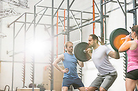 People assisting man in lifting barbell at crossfit gym