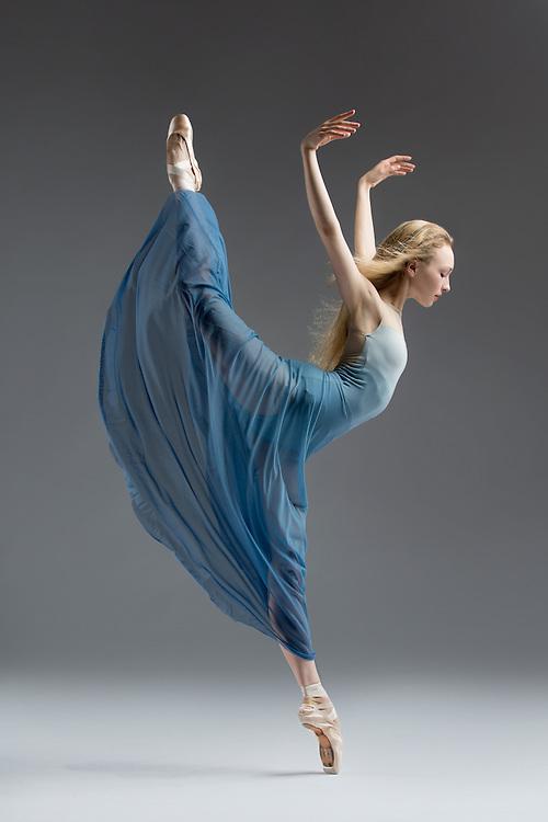 Classical ballet dancer, Nastia Alexandrova, in a blue romantic tutu, in the studio on a gray background. Photograph taken in San Francisco by Rachel Neville.