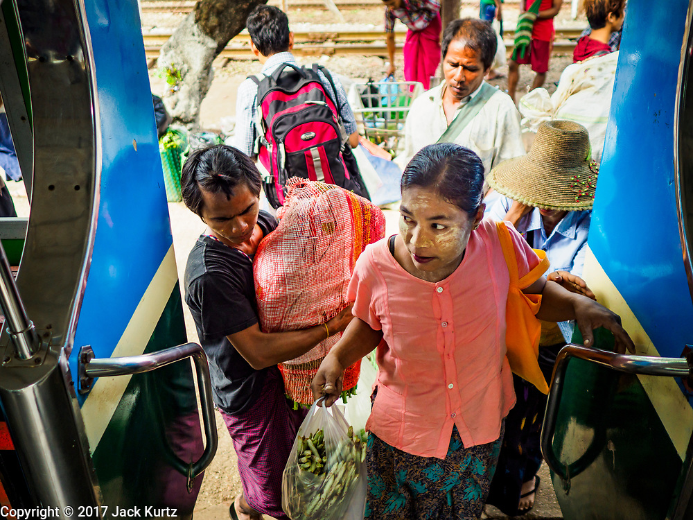 25 NOVEMBER 2017 - YANGON, MYANMAR: Passengers climb aboard the Yangon Circular Train in Danyingon station, in the middle of the train's loop. The Yangon Circular Train is a 45.9-kilometre (28.5 mi) 39-station two track loop system connects satellite towns and suburban areas to downtown. The train was built during the British colonial period, the second track was built in 1954. Trains currently run both directions (clockwise and counter-clockwise) around the city. The trains are the least expensive way to get across Yangon and they are very popular with Yangon's working class. About 100,000 people ride the train every day. A a ticket costs 200 Kyat (about .17¢ US) for the entire 28.5 mile loop.    PHOTO BY JACK KURTZ