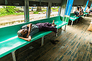 15 JUNE 2013 - YANGON, MYANMAR:  A man sleeps on a passenger seat on the Yangon Circular Train. The Yangon Circular Railway is the local commuter rail network that serves the Yangon metropolitan area. Operated by Myanmar Railways, the 45.9-kilometre (28.5mi) 39-station loop system connects satellite towns and suburban areas to the city. The railway has about 200 coaches, runs 20 times and sells 100,000 to 150,000 tickets daily. The loop, which takes about three hours to complete, is a popular for tourists to see a cross section of life in Yangon. The trains from 3:45 am to 10:15 pm daily. The cost of a ticket for a distance of 15 miles is ten kyats (~nine US cents), and that for over 15 miles is twenty kyats (~18 US cents). Foreigners pay 1 USD (Kyat not accepted), regardless of the length of the journey.     PHOTO BY JACK KURTZ
