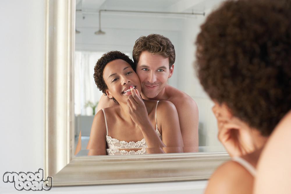 Man embracing woman applying lipstick in mirror