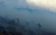 Firefighters try to establish a break along the hill above E. Trekker Rim Drive. A quick-moving brush fire near Columbia Village in Southeast Boise destoryed 10 homes, seriously damanged 9, and resulted in one death.