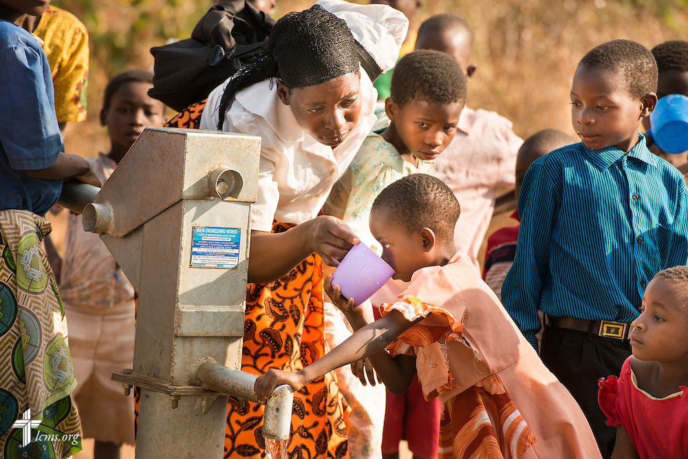 A women gives a sip of clean water pumped from an LCMS funded borehole well to a young girl on Sunday, Sept. 27, 2015, in Chingale, Malawi. LCMS Communications/Erik M. Lunsford
