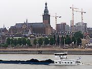 Een volgeladen binnenvaartschip vaart over de Waal langs de Waalkade in Nijmegen met op de achtergrond bouwkranen en de Stevenskerk.<br /> <br /> A fully loaded barge sails on the Waal along the Waalkade at Nijmegen with in the background cranes and the Stevenskerk.