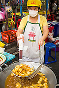 17 OCTOBER 2012 - BANGKOK, THAILAND:    A vegan wonton vendor deep fries vegan wontons during the Vegetarian Festival in Bangkok. The Vegetarian Festival is celebrated throughout Thailand. It is the Thai version of the The Nine Emperor Gods Festival, a nine-day Taoist celebration celebrated in the 9th lunar month of the Chinese calendar. For nine days, those who are participating in the festival dress all in white and abstain from eating meat, poultry, seafood, and dairy products. Vendors and proprietors of restaurants indicate that vegetarian food is for sale at their establishments by putting a yellow flag out with Thai characters for meatless written on it in red.        PHOTO BY JACK KURTZ