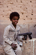 """Shibam, a children with a gun toy. The children familiarise early with guns. Declared Unesco World Heritage, this old city on the incense road is called the """"Manhattan of the desert"""" and is one of the most celebrated Arabic Islamic cities built in traditional style. A collection of nearly 500 skyscrapers built with mud bricks and 5-7 stores high."""