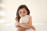 Girl cuddling teddy bear sitting on bed half length