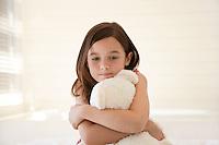 Girl cuddling teddy bear sitting on bed half length
