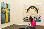 New York, NY - May 3, 2019. A woman on her phone matches a rainbow color in a painting shown by New York's Half Gallery  at the Frieze Art Fair on New York City's Randalls Island.