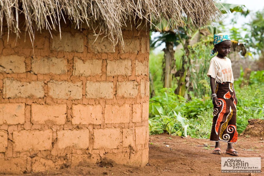 A girl stands by a mud brick house in the village of Tongo Gandima, near Bertoua, Cameroon, on Tuesday September 15, 2009.