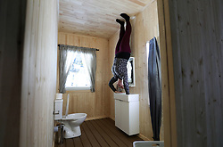 An employee holds onto the sink in the bathroom in 'The Upside Down House', a zero-gravity illusion experience, in The Triangle in Bournemouth, Dorset.