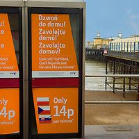 BT phone boxes advertising deals for calls to eastern europe near Hastings pier, East Sussex, England