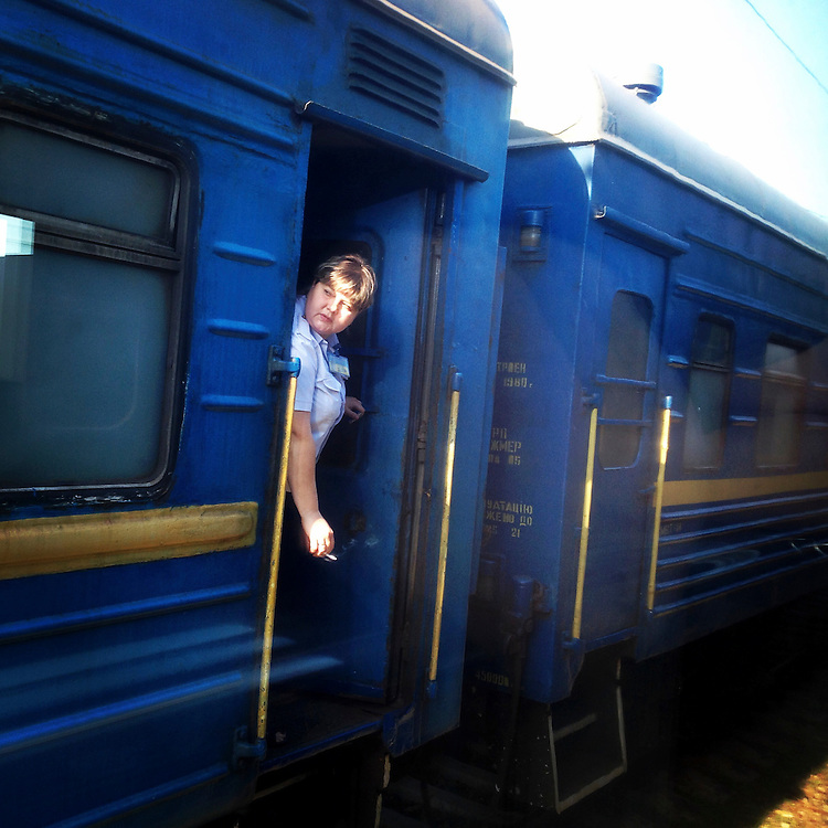 A train attendant leans out of a wagon as a destroyed bridge delays a trip from Kyiv to Donetsk on Sunday, July 27, 2014 in Yasinovataya, Ukraine.