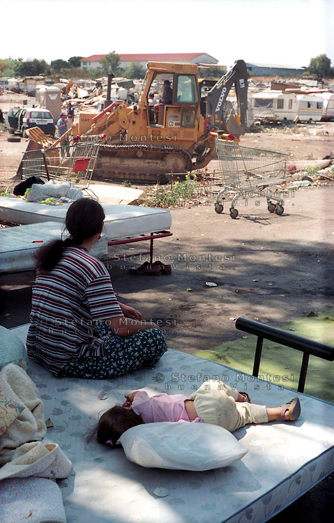 Rome May 17 th 2001   .Rom's camp of via Salone   .Vacated by the Municipal Police a Rom's camp of via Salone  demolishing with the bulldozers the residence of the Roms Romeni.The mother and child sleeping outdoors after the house demolition.Roma 17 Maggio 2001 .Campo rom  di Via salone.Sgomberato  dalla Polizia Municipale il campo rom di Via Salone demolendo con le ruspe le Abitazione dei Rom Romeni