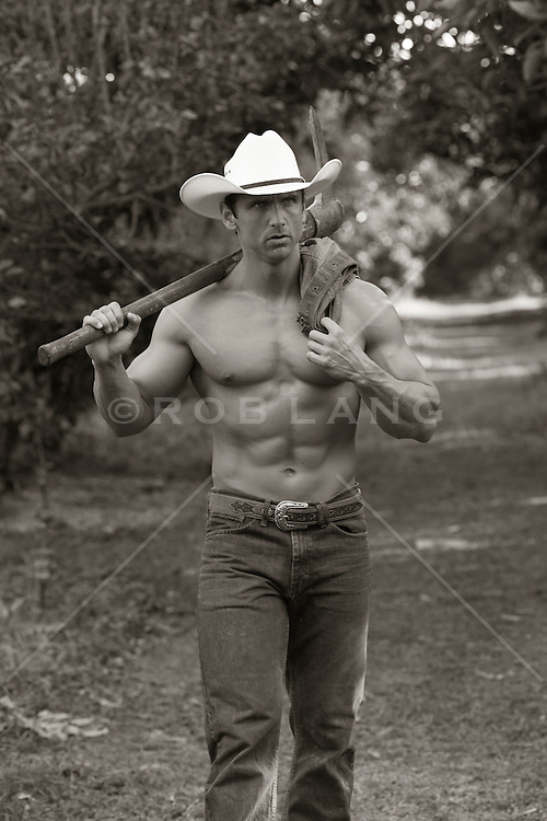 shirtless muscular cowboy walking with a pick axe
