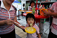 A Chinese child is fed instant noodles at a food stall at  the Olympic green in Beijing , China, Wednesday, Aug.20, 2008. It is one of the strangest things about the Olympics: From far away, it looks very close.Watching the Olympics on television, the athletes are right in front of you.  Up close, though, it's normally a different story. From the spectators' stands, the athletes are often just distant specks amid the enormity of some of the largest sports stadiums in the world. And there's so much else to grab your attention. There are snack bars, Coke machines, and life-sized cutouts of Chinese athletes with which you can pose. There are parades of Fuwas, the Olympic mascots. There are dancing fountains in front of the Water Cube, and thousands of volunteers to help you out. (Elizabeth Dalziel)