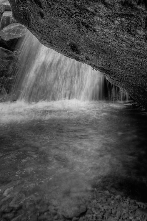 A black and white high dynamic range (HDR) image of a small waterfall viewed from beneath an overhanging boulder, Hog Camp Branch below Dark Hollow Falls, Shenandoah National Park, Virginia.
