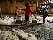 10 FEBRUARY 2016 - BAN LAEM, PHETCHABURI, THAILAND: Salt field workers carry freshly gathered salt into a salt barn in Phetchaburi province, Thailand. The salt harvest in Thailand usually starts in February and continues through May. Salt is harvested in many of the provinces along the coast, but the salt fields in Phetchaburi province are considered the most productive. The salt fields are flooded with sea water, which evaporates off leaving salt behind. Salt production relies on dry weather and producers are hoping the current drought will mean a longer harvest season for them.      PHOTO BY JACK KURTZ