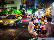 "30 MARCH 2013 - BANGKOK, THAILAND: A taxi drives past men eating at a street food stall in Bangkok. Thailand's economic expansion since the 1970 has dramatically reduced both the amount of poverty and the severity of poverty in Thailand. At the same time, the gap between the very rich in Thailand and the very poor has grown so that income disparity is greater now than it was in 1970. Thailand scores .42 on the ""Ginni Index"" which measures income disparity on a scale of 0 (perfect income equality) to 1 (absolute inequality in which one person owns everything). Sweden has the best Ginni score (.23), Thailand's score is slightly better than the US score of .45.   PHOTO BY JACK KURTZ"