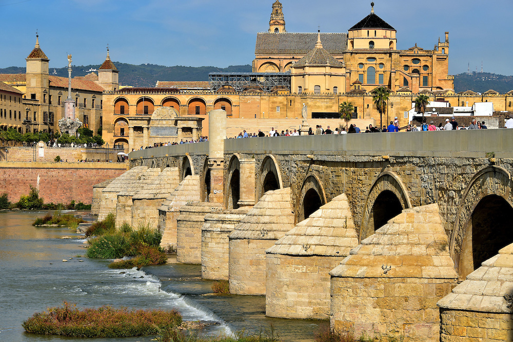Roman Bridge in C&oacute;rdoba, Spain<br /> The Roman Bridge derives its name from when it was built by command of Augustus. He was the first Emperor of the Roman Empire who reigned from 27 BC until 14 AD. The crossing over the Guadalquivir River was reconstructed in the early 8th century by Al-Samh, the Arab governor of Al-Andalus. This was the Muslim territory comprising most of today&rsquo;s Portugal and Spain. Additional renovations and expansions occurred during five centuries yet it has largely maintained its medieval appearance. The 820 foot length of Puente Romano is supported by 16 arches. The landmarks in the background are (left to right): The Bishop&rsquo;s Palace, Triumph of San Raphael, the Puerta de Puente and the Mosque-Cathedral.