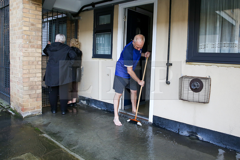 © Licensed to London News Pictures. 08/10/2019. London, UK. A resident sweeps water out of his flat following a burst water main on Brownswood Road in Finsbury Park, north London, causing flooding in a housing estate. . Emergency services and Thames Water are at the scene.  Photo credit: Dinendra Haria/LNP