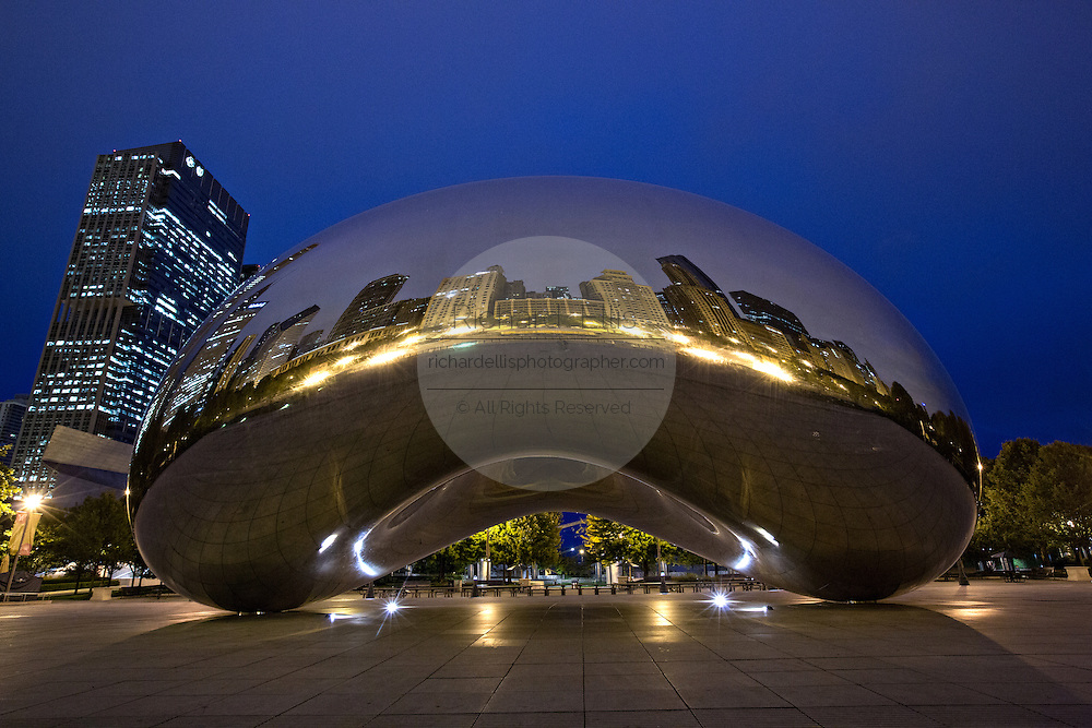 Cloud Gate Sculpture or The Bean with downtown skyline reflected in polished surface at twilight in Millennium Park in Chicago USA