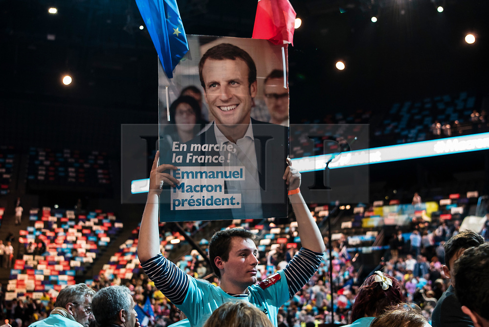 © London News Pictures. 17/04/2017. Paris, France. A man hods up a banner as French Presidential Candidate Emmanuel Macron addresses voters  at the Accorhotels Arena 6 days before the first round of presidential elections in France. Photo credit: Karine Pierre/LNP