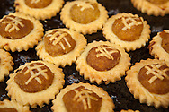 "Pineapple tarts are small, bite-size pastries filled with or topped with pineapple jam, popular in Singapore, Malaysia, Indonesia and Brunei. The Malaysian town of Malacca is particularly famous for producing good commercial pineapple tarts.  The pastry consists of a large proportion of butter and egg yolk, besides using corn starch, giving it a rich, buttery, tender and melt-in-the-mouth texture. The pineapple jam is usually made by slowly reducing and caramelizing grated fresh pineapple that has been mixed with sugar and spices - usually cinnamon, star anise and cloves. Typical shapes include a flat, open tart topped with pineapple jam under a lattice of pastry, rolls filled with jam that are open at the ends and jam-filled spheres.  Considered a ""festive cookie"", pineapple tarts are usually consumed during the Chinese New Year period. However, they are sold all year round by commercial bakeries and by souvenir stores serving tourists."