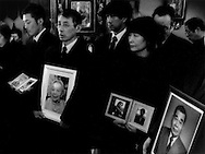 Church members hold portraits of their loved ones lost in the 11 March 2011 tsunami which struck Ishinomaki and this church one year before almost to the hour at a memorial service for the disaster at the Russian Orthodox Church.  Ishinomaki, Miyagi Prefecture, Japan.