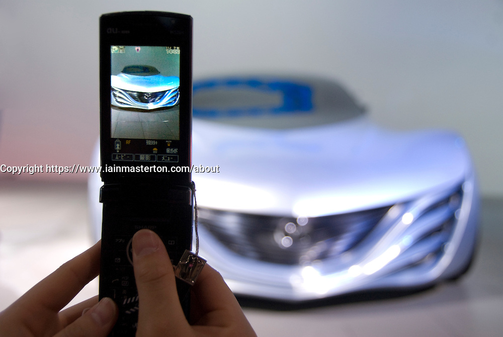 Visitor photographing Mazda Taiki concept sports car at Tokyo Motor Show 2007