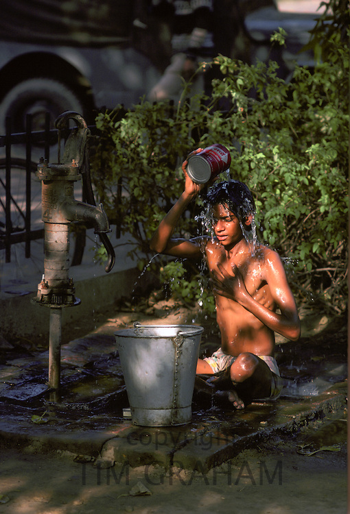 Boy having an early morning wash from a water pump in Delhi, India.